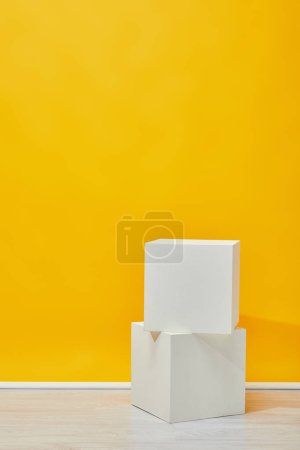 two plaster cubes arranged vertically near yellow wall