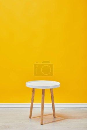 Foto de Mesa madera minimalista cerca de pared amarillo - Imagen libre de derechos