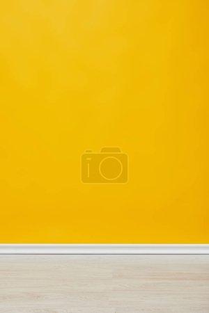 Photo pour Mur jaune vide lumineux avec plancher en bois - image libre de droit