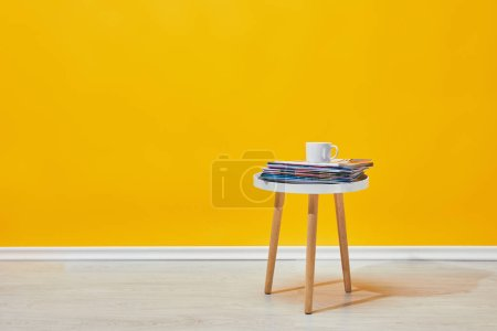 Photo for Little wooden table with pile of magazines and white cup of coffee near yellow wall - Royalty Free Image