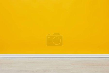 Photo pour Fond de mur jaune vide lumineux avec plancher en bois - image libre de droit
