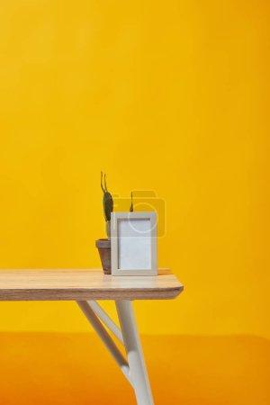 Photo pour Cadre photo vide et cactus en pot de fleurs sur jaune - image libre de droit