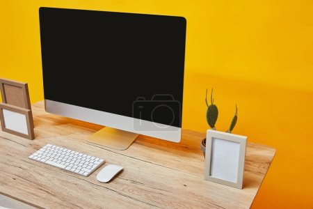 Computer, photo frames and cactus on wooden table on the background of yellow wall