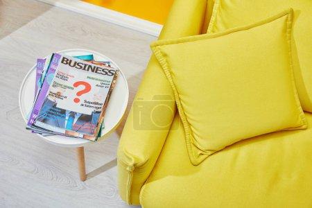 Foto de Cerca del sofá amarillo con cojines y mesa de centro con revistas de negocios - Imagen libre de derechos