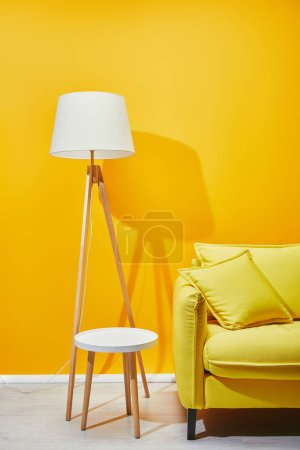 Sofa mit Kissen, Stehlampe und Couchtisch in der Nähe der gelben Wand