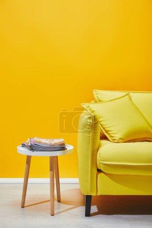 Canapé avec coussins et petite table avec les revues près de mur jaune