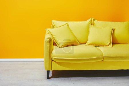 Sofa mit Kissen mit gelber Wand im Hintergrund