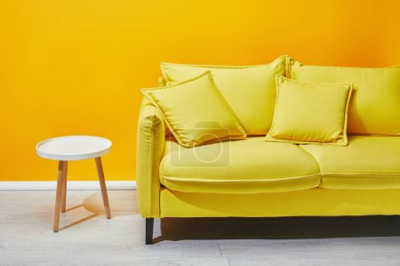 Yellow sofa and white coffee table near bright wall