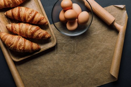 flat lay with eggs in bowl, tray with croissants, rolling pin and baking paper on black table