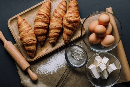 Photo for Elevated view of baking paper covered by flour, croissants and ingredients on table - Royalty Free Image