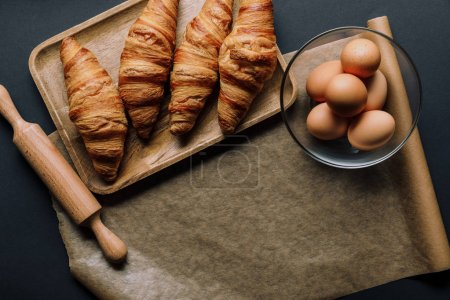Photo for Top view of tray with croissants, rolling pin and baking paper on black table - Royalty Free Image