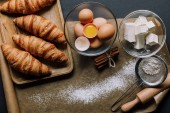 top view of baking paper covered by flour, croissants and ingredients on table