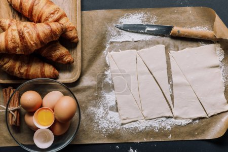 elevated view of baking paper with knife, dough for croissants, eggs and cinnamon on surface