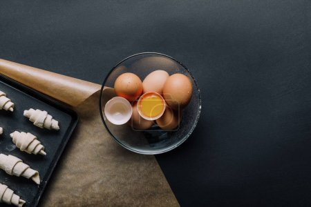 Photo for Elevated view of eggs in bowl and tray with dough for croissants on black table - Royalty Free Image