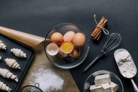 Photo for Top view of ingredients, eggs in bowl and tray with dough for croissants on black table - Royalty Free Image