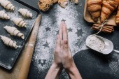 cropped image of woman rubbing flour between hand palms over table with dough for croissants on tray and ingredients