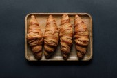 top view of tray with delicious croissants in bowl on black table