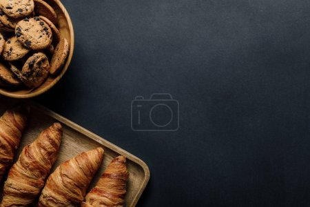 elevated view of tray with delicious croissants and cookies in bowl on black table