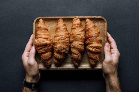 cropped image of man holding tray with croissants over black table