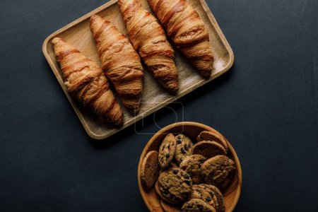 Photo for Top view of tray with delicious croissants and cookies in bowl on black table - Royalty Free Image
