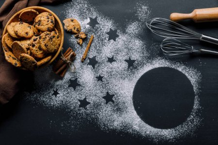 view from above of cookies in bowl, whisks and rolling pin on table covered by flour with symbol of stars