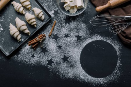 top view of tray with croissants, ingredients and whisks on table covered by flour with symbols of stars