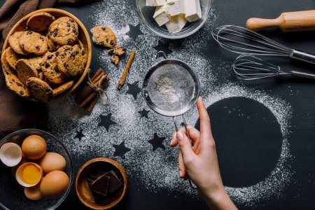 partial view of woman sifting flour through sieve over table covered by flour with symbols of stars and cookies with ingredients