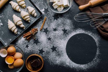 Foto de Vista desde arriba de la bandeja con la masa para croissants y los ingredientes sobre la mesa cubierta por harina con símbolos de estrellas - Imagen libre de derechos