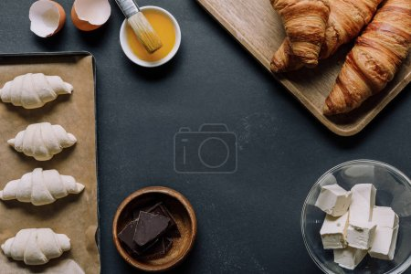 elevated view of ingredients, dough for croissants on tray, yolk with brush on black table
