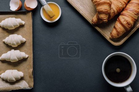 Photo for Top view of dough for croissants on tray, egg yolk with brush and coffee cup on black surface - Royalty Free Image
