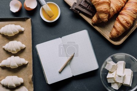 top view of blank textbook surrounded by dough for croissants and ingredients on table