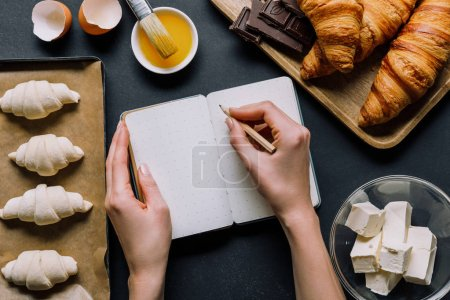 Photo for Partial view of woman writing recipe in textbook at table with dough for croissants on tray and ingredients - Royalty Free Image