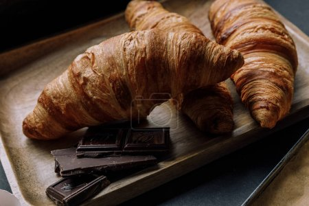 Photo for Close up view of chocolate and croissants on wooden tray - Royalty Free Image