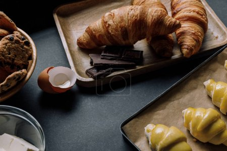close up view of dough for croissants on tray with baking paper surrounded by ingredients on black table