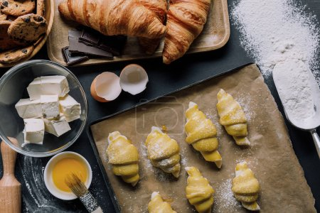 flat lay with dough for croissants on tray, yolk with brush and ingredients on table covered by flour