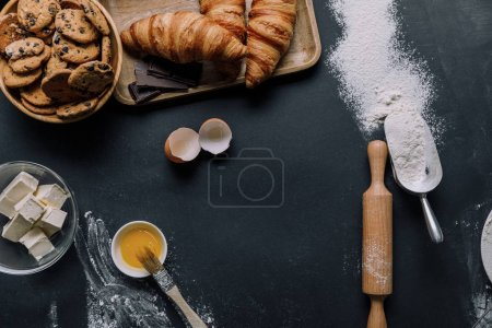 Photo for Flat lay with croissants, cookies and ingredients on black table with flour - Royalty Free Image