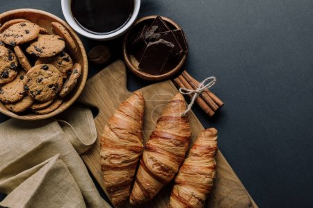 Photo pour Vue surélevée sur café, croissants, chocolat et biscuits sur table noire - image libre de droit
