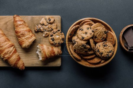 flat lay with arranged croissants, chocolate and cookies on black table