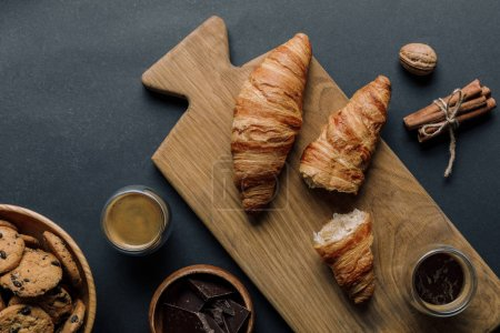 Photo for Elevated view of cinnamon, coffee, croissants, chocolate and cookies on black table - Royalty Free Image