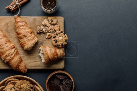 Photo for View from above of wooden board, coffee, croissants, chocolate and cookies on black table - Royalty Free Image