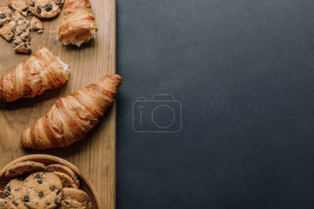 Photo for Top view of croissants and cookies with chocolate pieces in bowl on black table - Royalty Free Image