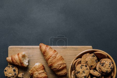 Photo for Flat lay with croissants and cookies with chocolate pieces in bowl on black table - Royalty Free Image