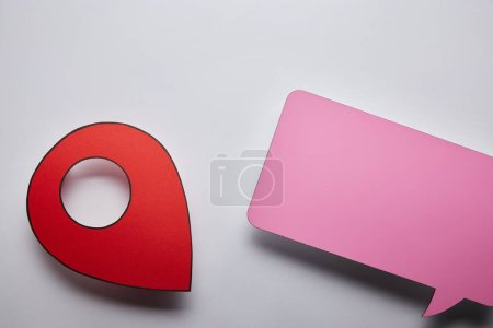 top view of empty pink speech bubble and red geo pin on grey background