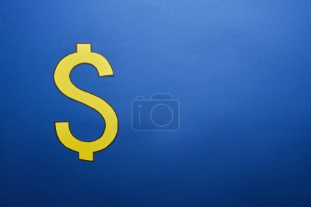 elevated view of yellow dollar sign on blue background