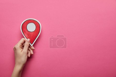 Photo for Top view of red geolocation in hand on pink background - Royalty Free Image