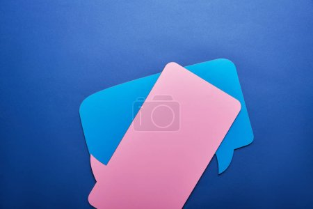 elevated view of empty blue and pink speech bubbles on blue background