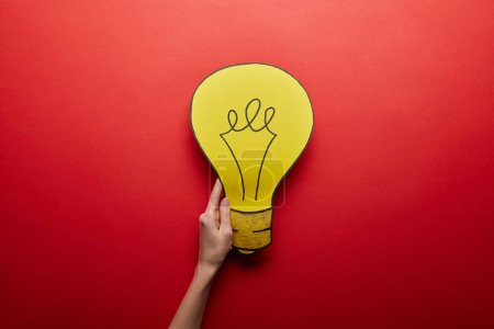 Photo for Top view of yellow light bulb made from paper idea symbol on red background - Royalty Free Image