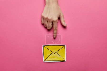Photo for Top view of hand pointing at yellow mail sign on pink background - Royalty Free Image
