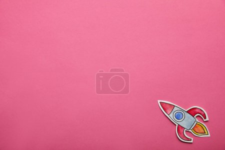 top view of flying rocket on pink background