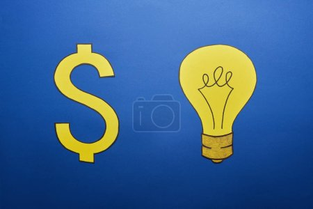 top view of yellow paper light bulb and dollar sign on blue background